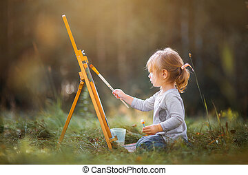 Little girl painting outdoors
