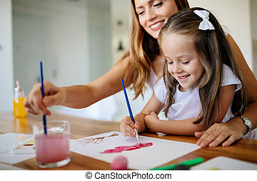 Little girl painting with her mother at home