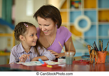 Little girl painting with mother