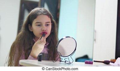 little girl paints lips with indoor lipstick . schoolgirl...