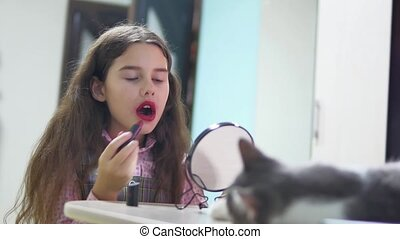 little girl paints lips with indoor lipstick . schoolgirl...