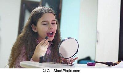 little girl paints lips with lipstick indoor. schoolgirl...
