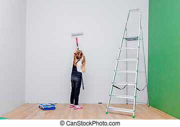 little girl paints the walls in the room with a roller