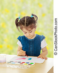 Little girl paints with watercolors at the table.