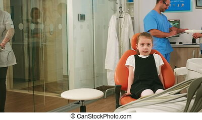 Little girl patient waiting pediatric stomatologist woman sitting in dental chair while man assistant talking with mother in background. Dentist discussing with girl before examining oral health.