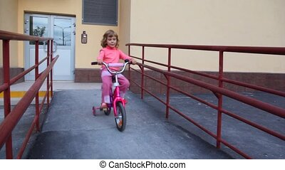 little girl pedaling on bicycle near apartment block