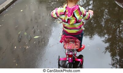 little girl pedaling on wet asphalt with puddles, camera...
