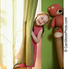 little girl peeking out from behind curtains - cheerful...