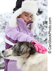 Little girl petting dog in the snow