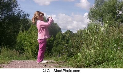 Little girl photographs in park.