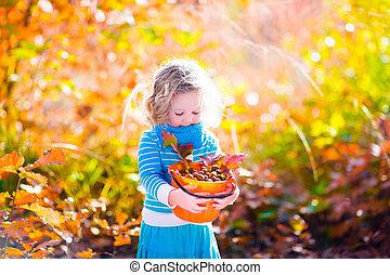 Little girl picking acorns in autumn park - Girl holding...