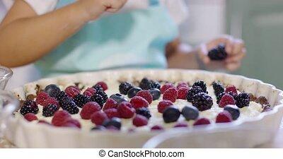 Little girl placing a blackberry on a pie - Little girl...