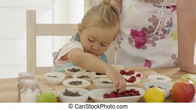 Little girl placing berries on muffins - Little girl placing...