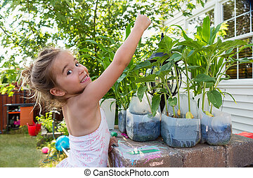 Little girl planting flowers in plastic bottles