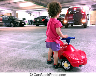 Little girl play with a toy car in parking lot.