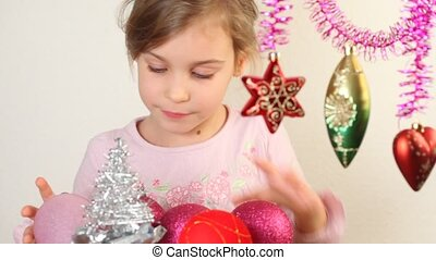 Little girl play with christmas-tree decoration