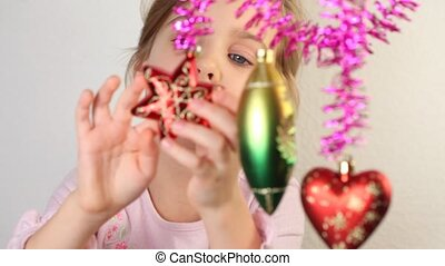 Little girl play with christmas-tree decoration, which hang.
