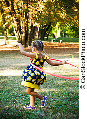 little girl play with hula hoop in park