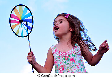 Little girl play with pinwheel  toy windmill