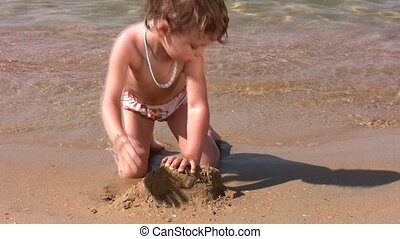 little girl play with sand on beach