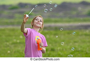 little girl play with soap bubbles