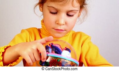 Little girl play with three-dimensional toy puzzle