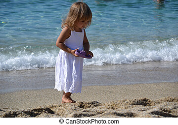 Little girl play with toy on the beach