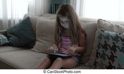 Little girl playing a game at the tablet