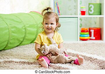 little girl playing and hugging loving pet kitten