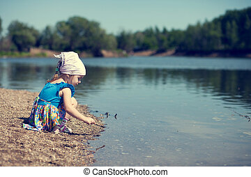 Little girl playing at the lake