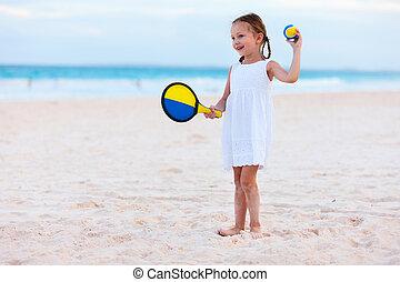 Little girl playing beach tennis