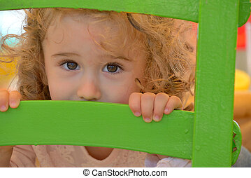 Little girl playing behind the chair