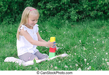 Little girl playing blocks in the park