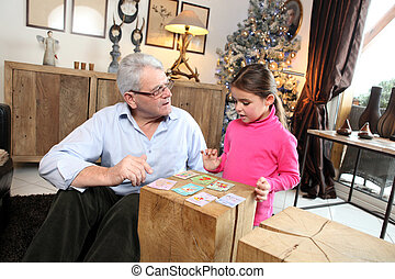 Little girl playing cards with her grandfather