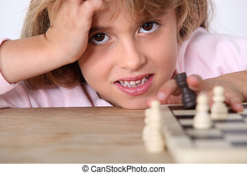 Little girl playing chess alone