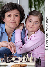 Little girl playing chess with grandmother