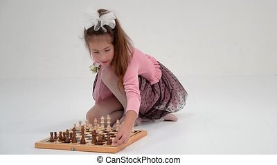 Little girl playing chess.On white background. - A little ...