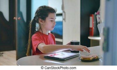 little girl playing digital tablet eating sandwiches. little...