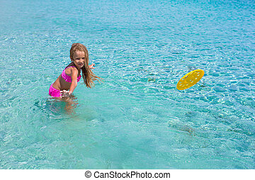 Little girl playing frisbee on tropical white beach during vacation