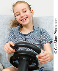 Little girl playing game with steering wheel.