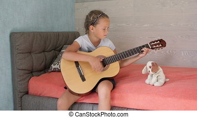 Little girl playing guitar and singing