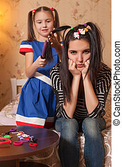 Little girl playing hairdresser with her mother.