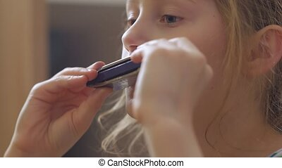 Little girl playing harmonica home interior closeup