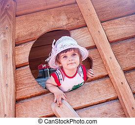 little girl playing in a wooden house