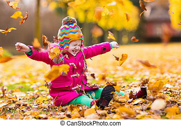 Little girl playing in autumn park - Happy little girl in ...