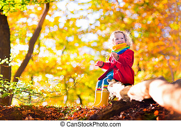 Little girl playing in autumn park - Little girl with yellow...