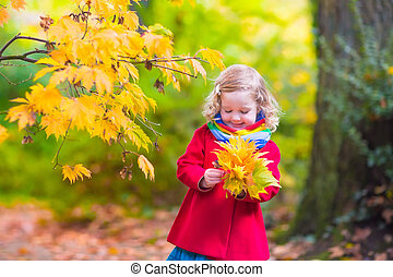 Little girl playing in beautiful autumn park
