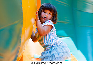 Little girl playing in inflatable bouncing castle
