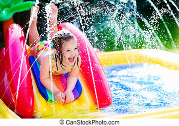 Little girl playing in inflatable garden swimming pool -...