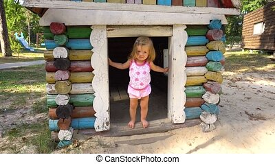 Little girl playing in small wooden house - Little girl...